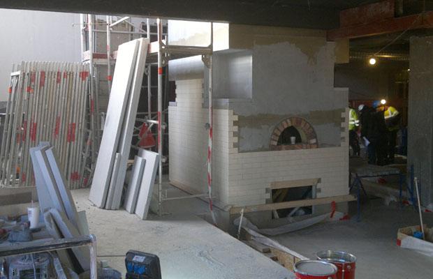 Stor pizzaovn som flislegges. Foto.